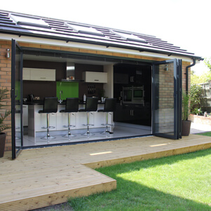 glazed doors opening onto decking and lawn