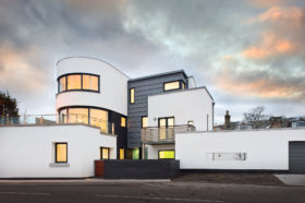 Art deco coastal home with white render and zinc cladding