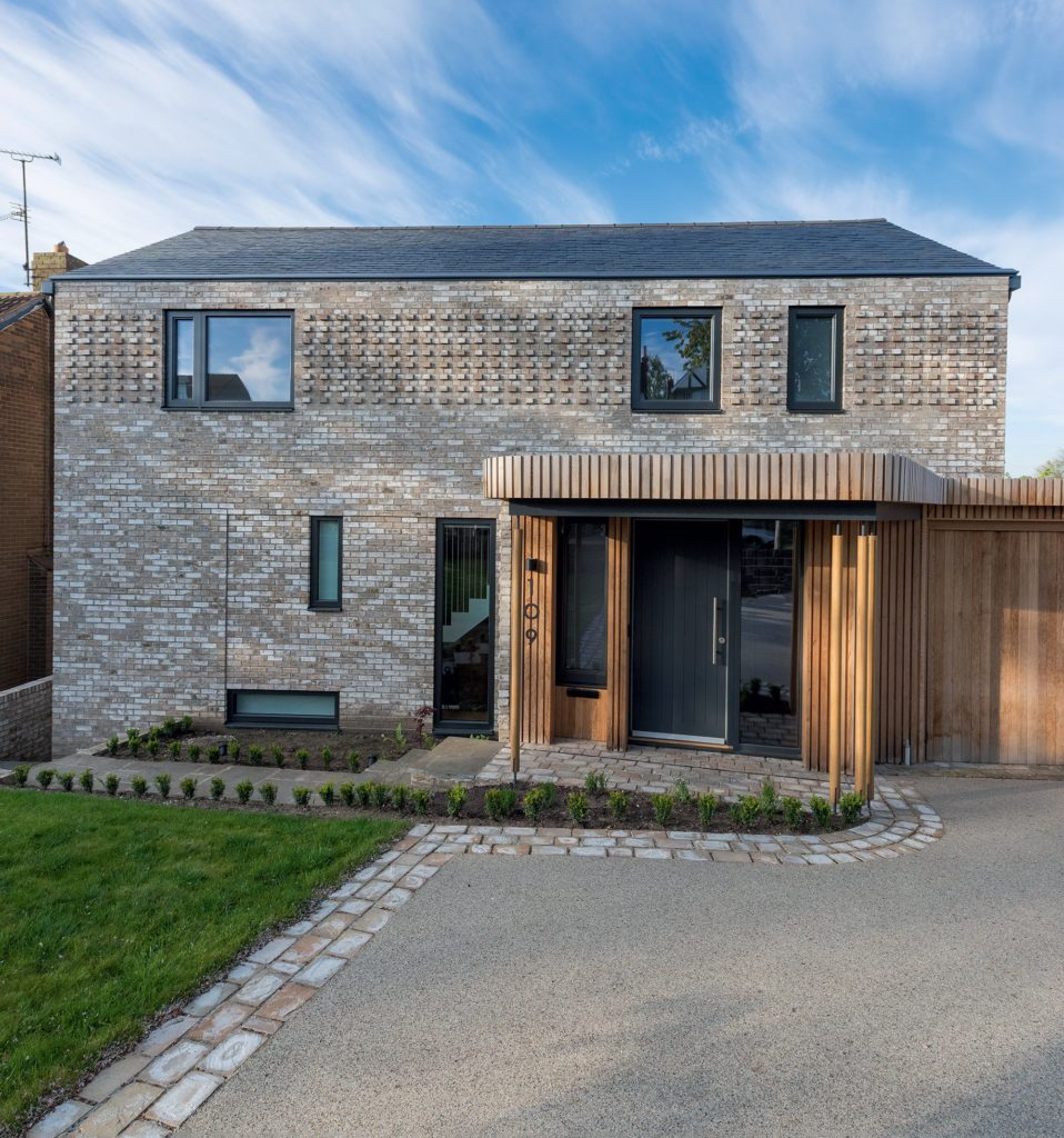 Grey brick detached home with slate roof
