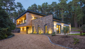 Fully integrated smart home as seen from outside clad in stone and timber