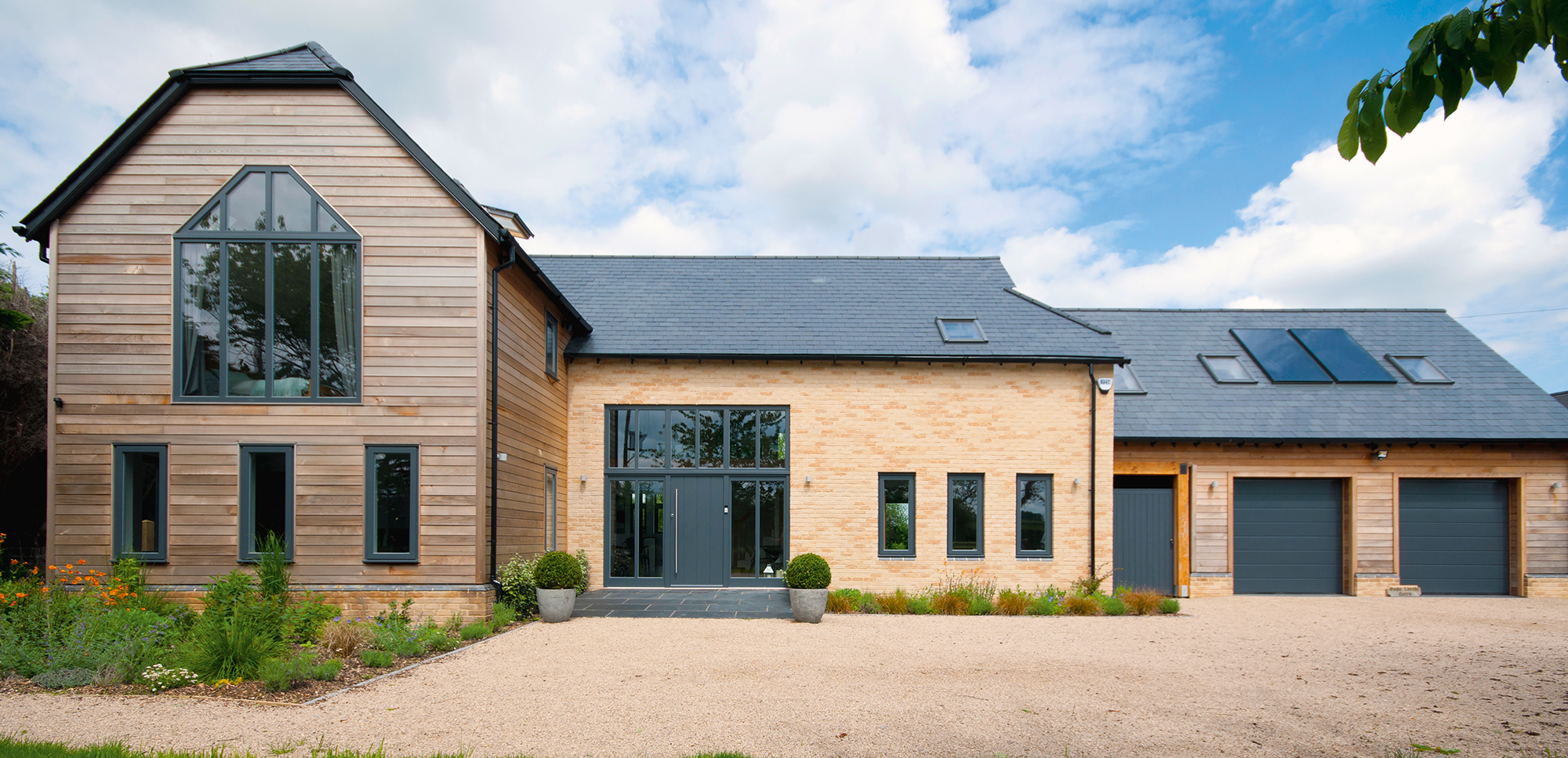 Timber frame home clad in timber and brick