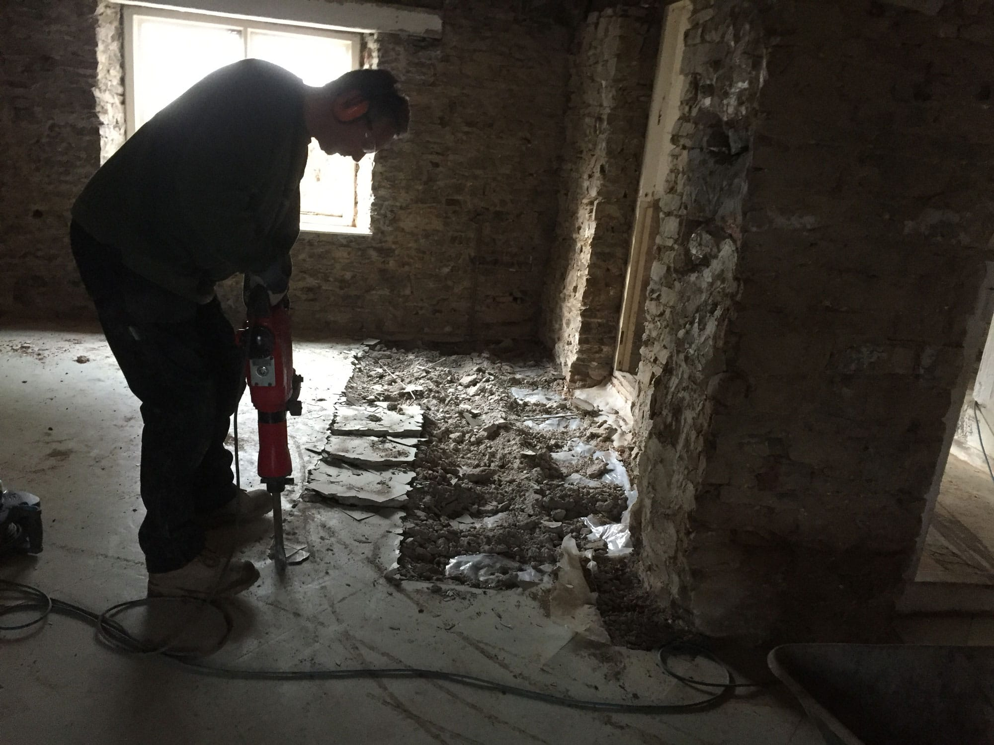 Man breaking up the floor in a period renovation